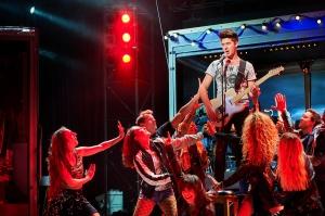 """Ganz oder gar nicht: Wenn die größten Hits von Wolfgang Petry zurück auf der Bühne kommen, soll das Publikum so restlos begeistert sein wie bei den großen Konzerten des Künstlers. Nach der Premiere von Wahnsinn! in Duisburg ist dieser Anspruch erfüllt. """"Ich habe Wolle gespürt"""", so eine glückliche Besucherin. Andere berichten: """"Beim Rausgehen hat das gesamte Publikum im Foyer weitergesungen"""". Und so haben wir die Münchner Laufzeit schon vor Start der Shows um eine Woche zu verlängert. Wahnsinn! – Das Musical mit den Hits von Wolfgang Petry ist nun bis einschließlich 3. Juni am Deutschen Theater zu erleben. Vor über 15 Jahren hat Wolfgang Petry die großen Bühnen der Welt verlassen und sich aus der Öffentlichkeit zurückgezogen. Sein musikalisches Lebenswerk jedoch ist immer noch allgegenwärtig. Seine schnellen Rhythmen und eindringlichen Liedtexte sind Stimmungsmacher auf jeder Party. Mit weit über 20 Millionen verkauften Alben ist und bleibt er einer der erfolgreichsten deutschen Interpreten und Songwriter überhaupt. Die Sehnsucht seiner Fans nach Live-Erlebnissen mit seinen Hits ist riesengroß. Im September 2016 feierte """"Wolle"""" seinen 65. Geburtstag, was die Macher von WAHNSINN! zum Anlass nehmen, ihm ein besonderes Geschenk zu machen: Wolfgang Petrys Songs finden den Weg zurück auf die große Showtribühne. Das brandneue Musical präsentiert die größten Erfolge des Schlager-Giganten auf der Theaterbühne. Nach seiner Uraufführung in Duisburg und einem Gastspiel in Berlin feiert es Mitte Mai 2018 seine bayerische Premiere am Deutschen Theater. """"WAHNSINN!"""" ist das erste Party-Schlager-Musical der Welt. Ein Stück zum Spaßhaben und eine Geschichte mit großen Gefühlen, über Freundschaft und Familie und die Höhen und Tiefen, die das Jungfühlen, das Erwachsensein, das Leben - so wie es ist - mit sich bringt: Eine emotionale, humorvolle und turbulente Story, eingebettet in über 25 Hits von Wolfgang Petry, wie """"Verlieben, verloren, vergessen, verzeih'n"""", """"Der Himmel brennt"""", """"We"""